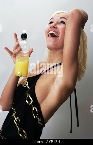 Blond woman with a juice bottle | Blonde lachende Frau mit einer Saftflasche - Stock Photo