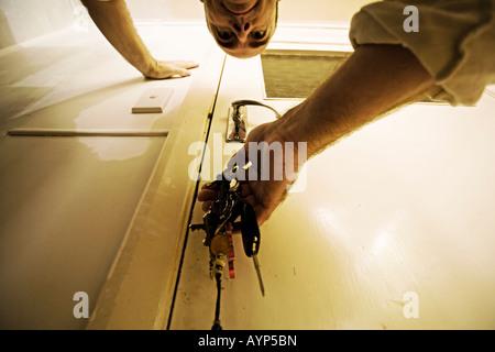 Man puts keys in door - Stock Photo