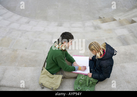 Young couple sitting on steps while making notes - Stock Photo