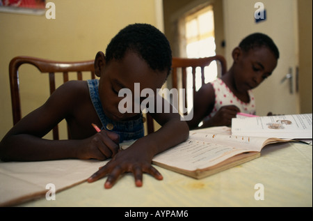 UGANDA East Africa Kampala Children Education Two young boys sitting at table at home doing homework writing and - Stock Photo