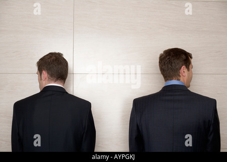 Two businessmen standing in front of a wall - rear view - Stock Photo