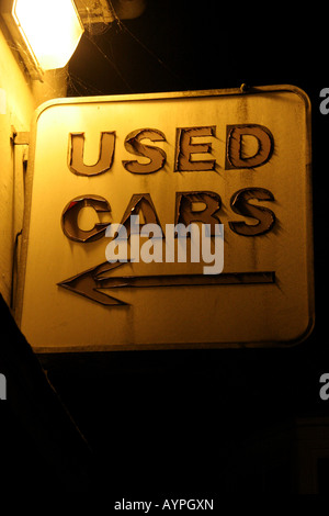Used car sales sign showing serious signs of wear with arrow pointing left - Stock Photo