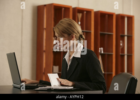 A blonde businesswoman looking at her laptop with a appointment diary beside her - Stock Photo