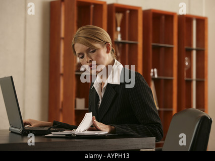 A blonde businesswoman looking at her appointment diary with a laptop beside her - Stock Photo