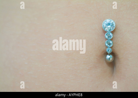 A small jewelry is pierced on a navel - Stock Photo