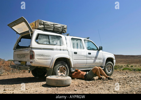 Changing a flat tire on an off-road vehicle (4X4) in northern Namibia, Africa - Stock Photo