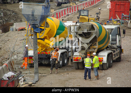 London Docklands redevelopment building site ready mix concrete delivery trucks - Stock Photo