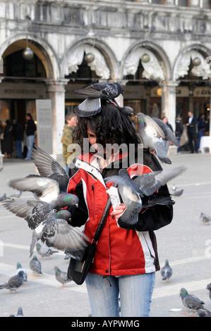 Feeding pigeons at St. Marks Square, Venice, Veneto, Italy, Europe - Stock Photo