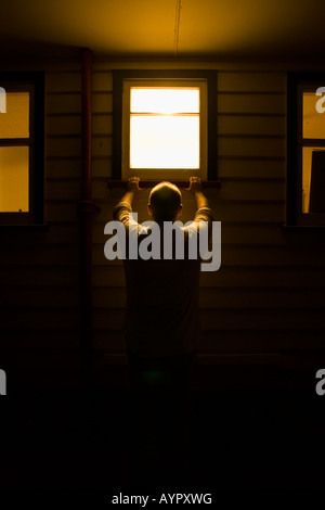 Man looks into house window at night. Full model and property release. - Stock Photo