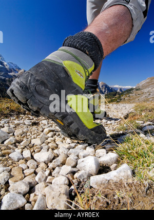 Yellow leather mountain climbing shoes, hiker on a trail wearing hiking boots, Bolzano-Bolzen, Italy - Stock Photo