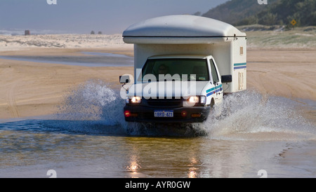 Off-road camper (4X4 RV) driving through the water on the beach at Fraser Island, Queensland, Australia - Stock Photo