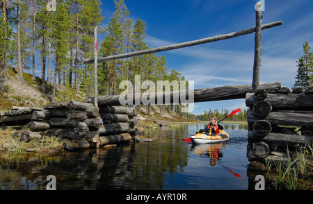 Woman paddling on a canal underneath a little wooden bridge, Femundsmarka National Park, Femundsmark, Norway - Stock Photo