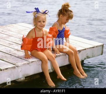 Two 5 year old girls waring bathing suits and water wings sitting on dock with feet in water - Stock Photo