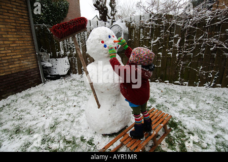 Three year old girl making a snowman in her garden - Stock Photo