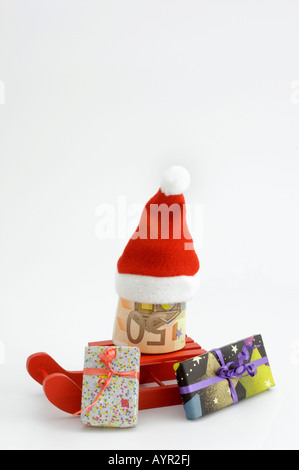 Christmas, red sleigh with 50-Euro bills rolled up, Santa hat and wrapped presents - Stock Photo