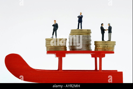 Businessmen standing on stacks of Euro coins on a red sleigh - Stock Photo