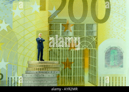 Satisfied-looking businessman standing on a stack of coins in front of a 200-Euro bill - Stock Photo