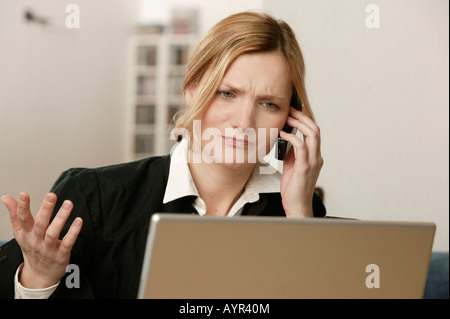 Young blonde woman in front of laptop, talking on phone - Stock Photo