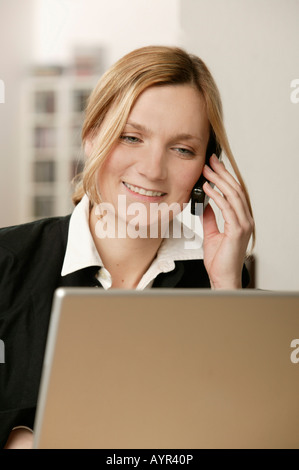 Young blonde woman in front of laptop, talking on phone, smiling - Stock Photo