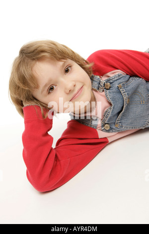 Eight-year-old girl lying on the floor - Stock Photo