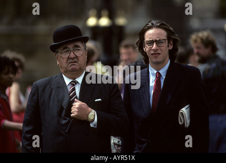 Older man wearing bowler hat and young man wearing pin-striped suit with newspaper under his arm walking in London, - Stock Photo