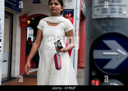 Indian woman walking on a sidewalk in Little India Singapore - Stock Photo