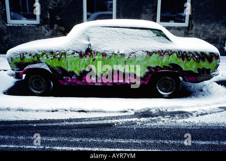 Brightly-coloured, snow-covered car parked on the side of a street in Vienna, Austria, Europe - Stock Photo