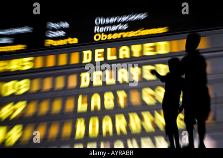 Two children aged six and ten looking at a flight information board, delayed flights - Stock Photo