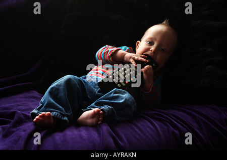 Six month old baby boy with the remote control on the couch - Stock Photo