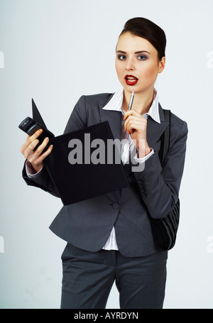 Young businesswoman, female manager with purse and folder, pondering - Stock Photo