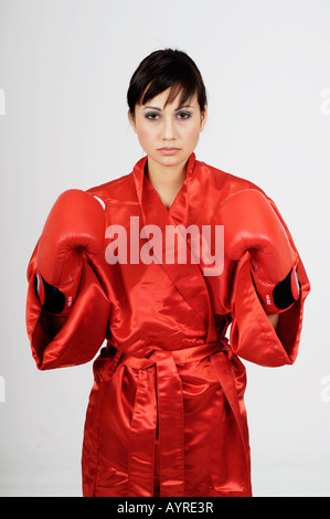 Young female boxer wearing red cloak in starting position - Stock Photo