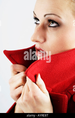 Young woman wearing red coat pulling up her collar - Stock Photo