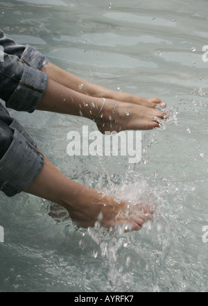 Two pairs of female feet splashing water in a fountain. - Stock Photo