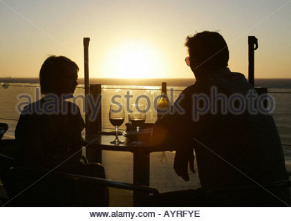 Couple sitting on the terrace of the Blue Duck Restaurant in Fremantle, Western Australia watching the sun set. - Stock Photo