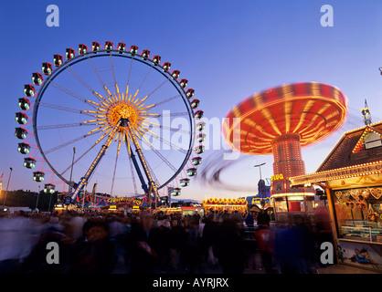 Ferris wheel and swing carousel, Oktoberfest (Octoberfest Munich Beer Festival), Munich, Germany - Stock Photo