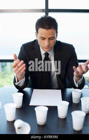 Reflective businessman sitting at table with plastic cups of coffee - Stock Photo
