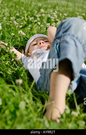 Girl laying on a cloverleaf meadow, daydreaming in summertime - Stock Photo