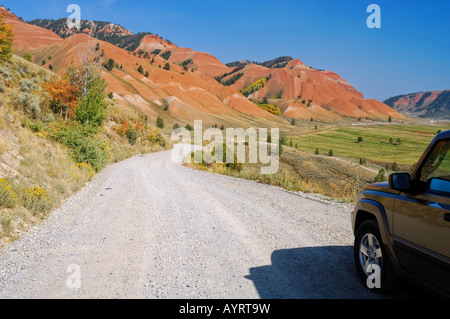 Car driving along a gravel road, Greater Yellowstone Ecosystem, Wyoming, USA - Stock Photo