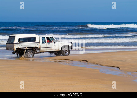 Off-road pick-up truck driving on the beach, Fraser Island, Queensland, Australia - Stock Photo