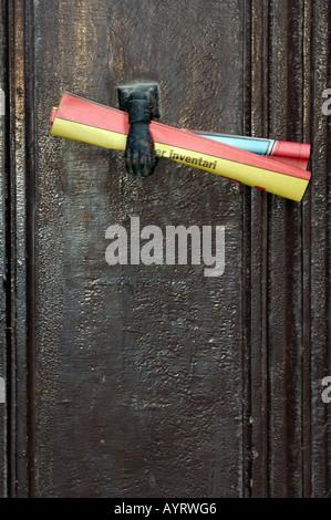 junk mail flyer paper held by door knocker on slid front door in spain - Stock Photo
