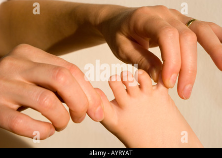 Woman's hands tugging at child's toes - Stock Photo