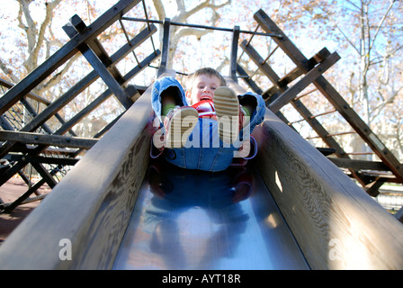 looking up a park slide at a young boy coming down with his feet in the air - Stock Photo