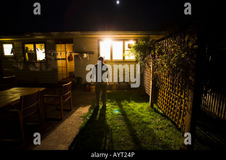 Watching through the window, man looks in house from garden at night in darkness - Stock Photo