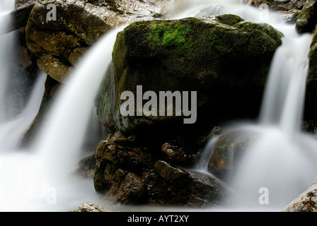 Water spray over moss-covered rocks, Kuhflucht Falls, Farchant, Bavaria, Germany, Europe - Stock Photo
