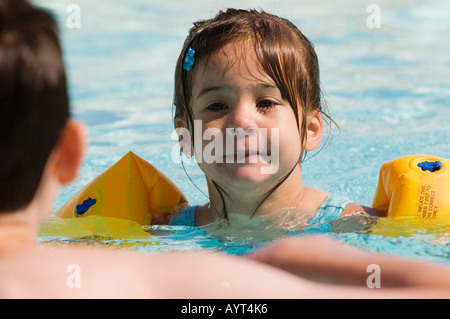 girl age 4 learning to swim and playing in a swimming pool wearing floats floatation device - Stock Photo