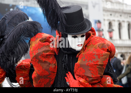 Colourful red-and-black costume and large top hat, mask and feathers, Carnevale di Venezia, Carneval in Venice, - Stock Photo