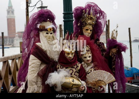 Family, two adults and two children, wearing purple and gold costumes, Carnevale di Venezia, Carneval in Venice, - Stock Photo