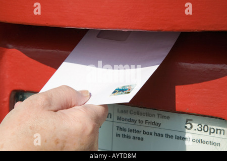 England UK Close-up of person's hand holding letter with 2nd class stamp to post in red postbox - Stock Photo