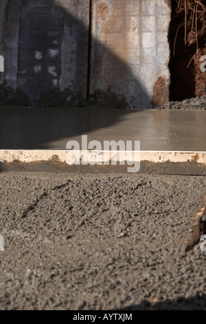 piece of wood used to level off concrete whilst laying concrete base - Stock Photo