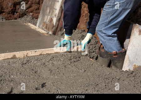 workman in protective boots and gloves uses piece of wood used to level off concrete whilst laying concrete base - Stock Photo